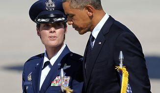 Colonial Kristin Goodwin, Vice Commander of the 509th Bomb Wing, left, walks with President Barack Obama after arriving at Whiteman Air Force Base in Knob Noster, Mo., Wednesday, July 24, 2013. Obama is traveling to the University of Central Missouri to deliver a speech focusing on the economy.  (AP Photo/Colin E. Braley)