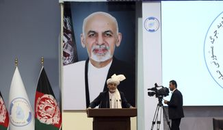 Backdropped by his own image, Afghan President Ashraf Ghani speaks to delegates during the first day of the Afghan Loya Jirga meeting in Kabul, Afghanistan, Monday, April 29, 2019.  Afghanistan's president Ashraf Ghani opened the Loya Jirga grand council on Monday with more than 3,200 prominent Afghans attending to seek an agreed common approach for future peace talks with the Taliban, but the gathering may further aggravate divisions within the U.S.-backed government. (AP Photo/Rahmat Gul)