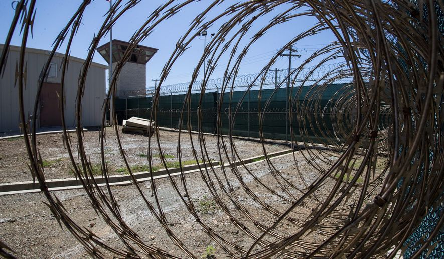 In this photo reviewed by U.S. military officials, the control tower is seen through the razor wire inside the Camp VI detention facility, Wednesday, April 17, 2019, in Guantanamo Bay Naval Base, Cuba. (AP Photo/Alex Brandon)