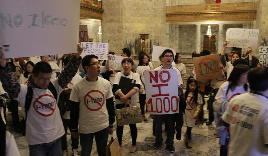 """Opponents of an initiative to the Legislature that would allow the state to use hiring and recruitment goals, but not quotas, to bring minority candidates into state jobs, education and contracting march and chant """"Shame on you!"""" outside the Senate chambers after the Senate passed the measure, Sunday, April 28, 2019, in Olympia, Wash. The measure loosens restrictions enacted in a separate 1998 initiative that banned government discrimination or preferential treatment based on factors like race or gender. (AP Photo/Rachel La Corte)"""