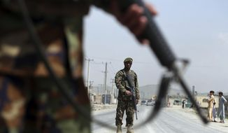 in this Sunday, April 28, 2019, file photo, Afghan National Army soldiers stand guard at a checkpoint on the Jalalabad-Kabul road, on the outskirts of Kabul, Afghanistan. (AP Photo/Rahmat Gul) ** FILE **