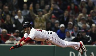 Boston Red Sox's Andrew Benintendi dives for home plate as he beats the throw to score on a sacrifice fly by Xander Bogaerts during the eighth inning of a baseball game against the Oakland Athletics at Fenway Park, Monday, April 29, 2019, in Boston. (AP Photo/Charles Krupa)