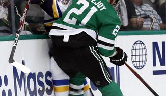 St. Louis Blues' Robert Thomas (18) is checked against the boards by Dallas Stars' Ben Lovejoy (21) during the second period in Game 3 of an NHL second-round hockey playoff series, Monday, April 29, 2019, in Dallas. (AP Photo/Tony Gutierrez)