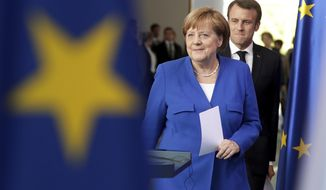 German Chancellor Angela Merkel and the President of France Emmanuel Macron arrive for a joint press conference on occasion of a meeting of Balkan leaders at the chancellery in Berlin, Monday, April 29, 2019. German Chancellor Angela Merkel and French President Emmanuel Macron are hosting the meeting to restart deadlocked talks between Serbia and Kosovo. (AP Photo/Michael Sohn)