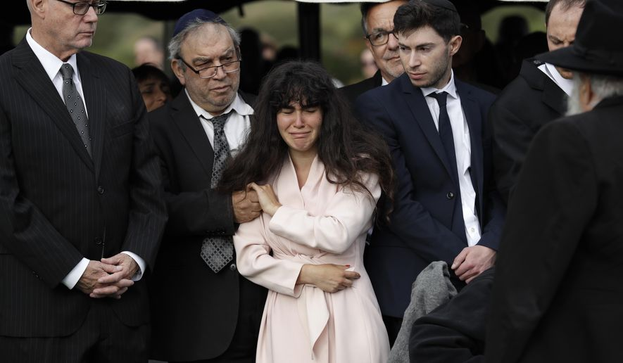Hannah Kaye, the daughter of shooting victim Lori Kaye, center, holds the hand of her father, Howard Kaye, during funeral services, Monday, April 29, 2019, in San Diego. Lori Kaye was killed when a man opened fire several days earlier inside a synagogue near San Diego, as worshippers celebrated the last day of a major Jewish holiday. (AP Photo/Gregory Bull)