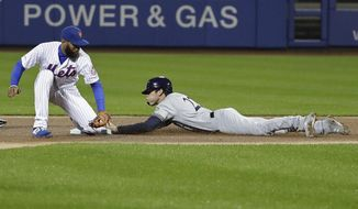 Milwaukee Brewers' Christian Yelich, right, beats the tag by New York Mets shortstop Amed Rosario to steal second base during the first inning of a baseball game Friday, April 26, 2019, in New York. (AP Photo/Frank Franklin II)