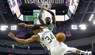Boston Celtics' Jaylen Brown dunks over Milwaukee Bucks' Giannis Antetokounmpo during the second half of Game 1 of a second round NBA basketball playoff series Sunday, April 28, 2019, in Milwaukee. The Celtics won 112-90 to take a 1-0 lead in the series. (AP Photo/Morry Gash) **FILE**