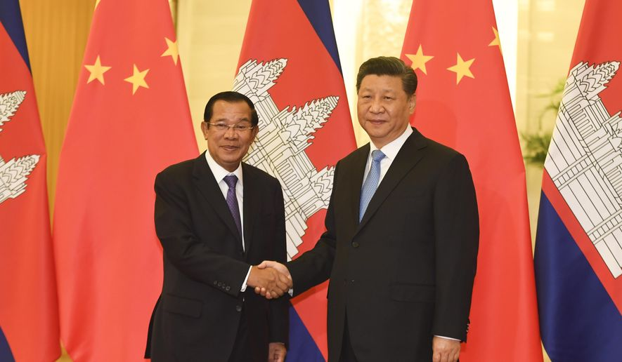 Cambodia's Prime Minister Hun Sen, left, shakes hands with China's President Xi Jinping before their meeting at the Great Hall of the People, Monday, April 29, 2019, in Beijing. (Madoka Ikegami/Pool Photo via AP)