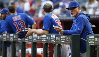 FILE - In this Friday, April 26, 2019, file photo, Chicago Cubs manager Joe Maddon, right, looks on from the dugout prior to the start of a baseball game against the Arizona Diamondbacks, in Phoenix. Maddon is doing his lineups three days at a time, giving his players an advance look at what to expect for the upcoming series. (AP Photo/Ralph Freso, File)