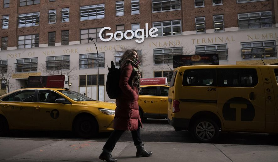 FILE- In this Dec. 17, 2018, file photo a woman walks past Google offices in New York. Alphabet Inc., parent company of Google, reports financial results on Monday, April 29, 2019. (AP Photo/Mark Lennihan, File)
