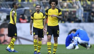 Dortmund's Axel Witsel and Dortmund's Paco Alcacer leave the pitch disappointed after losing the German Bundesliga soccer match between Borussia Dortmund and FC Schalke 04 in Dortmund, Germany, Saturday, April 27, 2019. Dortmund was defeated in the Derby by Schalke with 2-4. (AP Photo/Martin Meissner)