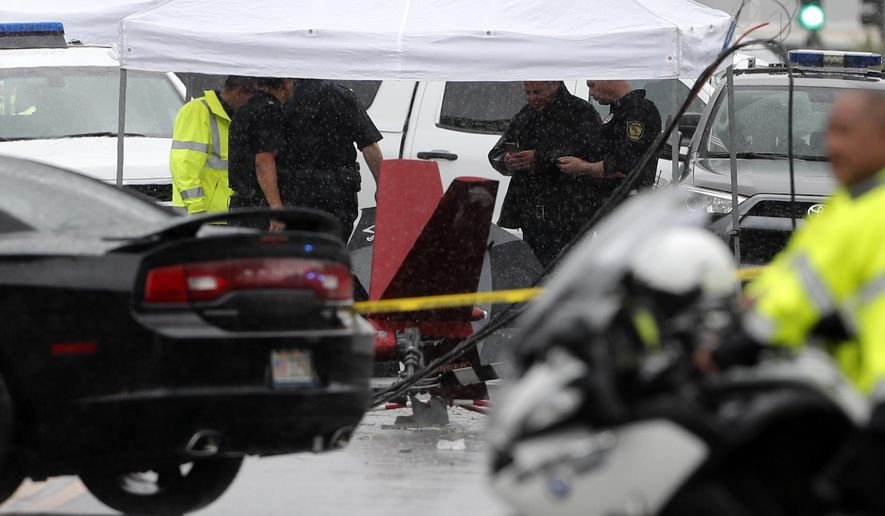 Investigators stand around the wreckage of a helicopter, Monday, April 29, 2019, in Kailua, Hawaii. Fire and helicopter parts rained from the sky Monday in a suburban Honolulu community in a crash that killed three people aboard, officials and witnesses said. (AP Photo/Marco Garcia)