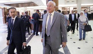 Former Malaysian Prime Minister Najib Razak, center, walks in a courtroom at Kuala Lumpur High Court in Kuala Lumpur, Malaysia, Monday, April 29, 2019. Najib, his former deputy and several high-ranking former officials have already been charged with corruption after the election ushered in the first change of power since Malaysia's independence from Britain in 1957. (AP Photo/Vincent Thian)