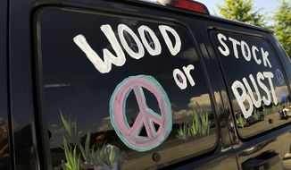 "This Aug. 14, 2009, file photo shows a van decorated with ""Woodstock or Bust"" at the original Woodstock Festival site in Bethel, N.Y. (AP Photo/Stephen Chernin, File)"