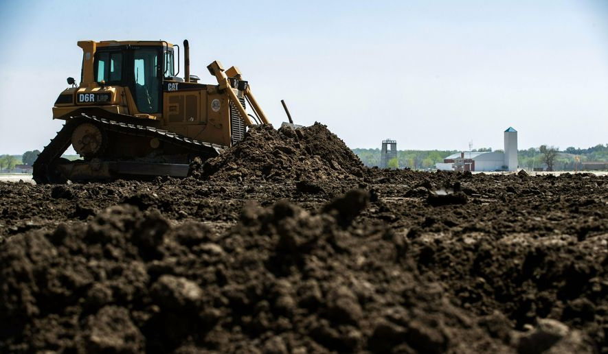 In this April 24, 2019, photo crews fill areas around the levee with dirt at the  flood-prone Camp Ashland training site camp in Ashland, Neb. (Brendan Sullivan/Omaha World-Herald via AP)