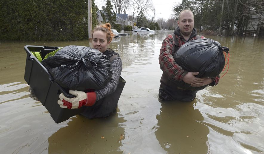 Residents Lawrence Courville, left, and Andy Goulet carry belongings down a flooded street in Ste-Marthe-sur-le-Lac, Quebec, Sunday, April 28, 2019. (Ryan Remiorz/The Canadian Press via AP)