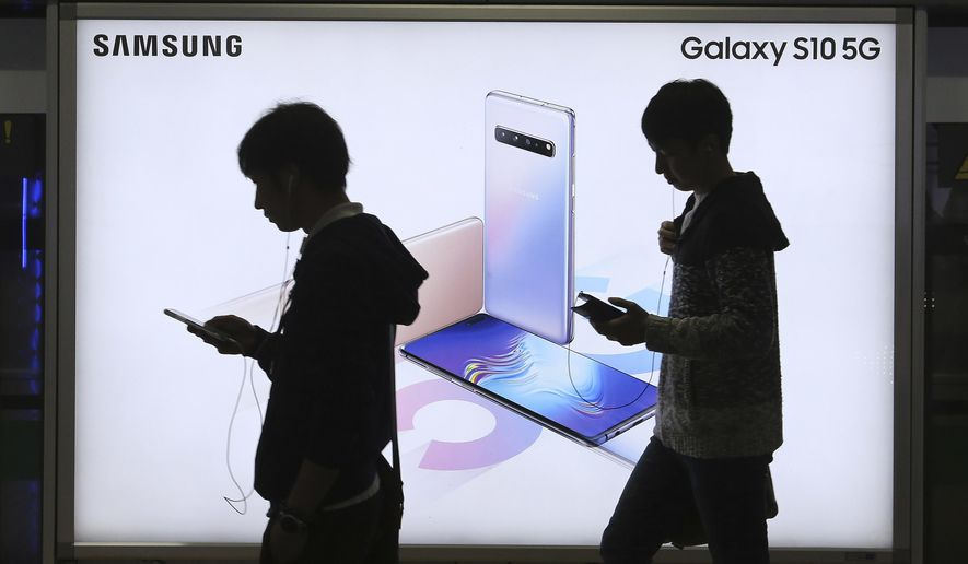 People pass by an advertisement of Samsung Electronics' Galaxy S10 5G smartphone at a subway station in Seoul, South Korea, Tuesday, April 30, 2019. Samsung Electronics Co. says its operating profit for the last quarter declined more than 60% from a year earlier because of falling chip prices and sluggish demands for its display panels. (AP Photo/Ahn Young-joon)