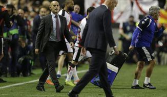 Rayo Vallecano's coach Paco Jemez, left, looks over to Real Madrid's coach Zinedine Zidane as he walks off the pitch at the end of a Spanish La Liga soccer match between Rayo Vallecano and Real Madrid at the Vallecas stadium in Madrid, Spain, Sunday, April 28, 2019. Rayo won the match 1-0. (AP Photo/Paul White)