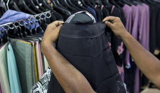 A salesman covers the face of a mannequin with a niqab cafe veil at a women's clothing shop in Kattankudy, Sri Lanka, Monday, April 29, 2019. After being targeted by Islamic State suicide bombings on Easter, Sri Lanka has banned the niqab face veil, which increasingly has been seen in Muslim areas of the island nation's east. (AP Photo/Gemunu Amarasinghe)