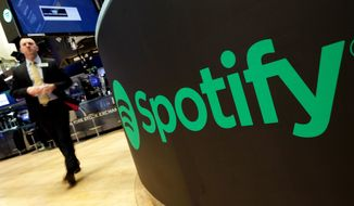 "FILE - In this Tuesday, April 3, 2018 file photo, a trading post sports the Spotify logo on the floor of the New York Stock Exchange. Music streaming service Spotify says the number of its paying subscribers has hit 100 million for the first time, up 32% on the year and almost twice the latest figures for Apple Music. The Stockholm-based company called the figure, which was reached during the first three months of 2019, ""an important milestone."" (AP Photo/Richard Drew, File)"