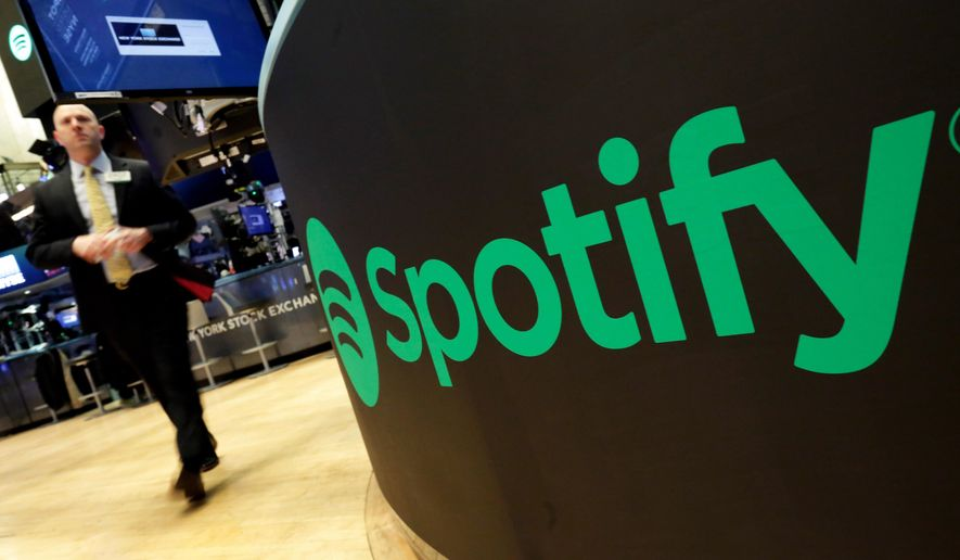 """FILE - In this Tuesday, April 3, 2018 file photo, a trading post sports the Spotify logo on the floor of the New York Stock Exchange. Music streaming service Spotify says the number of its paying subscribers has hit 100 million for the first time, up 32% on the year and almost twice the latest figures for Apple Music. The Stockholm-based company called the figure, which was reached during the first three months of 2019, """"an important milestone."""" (AP Photo/Richard Drew, File)"""