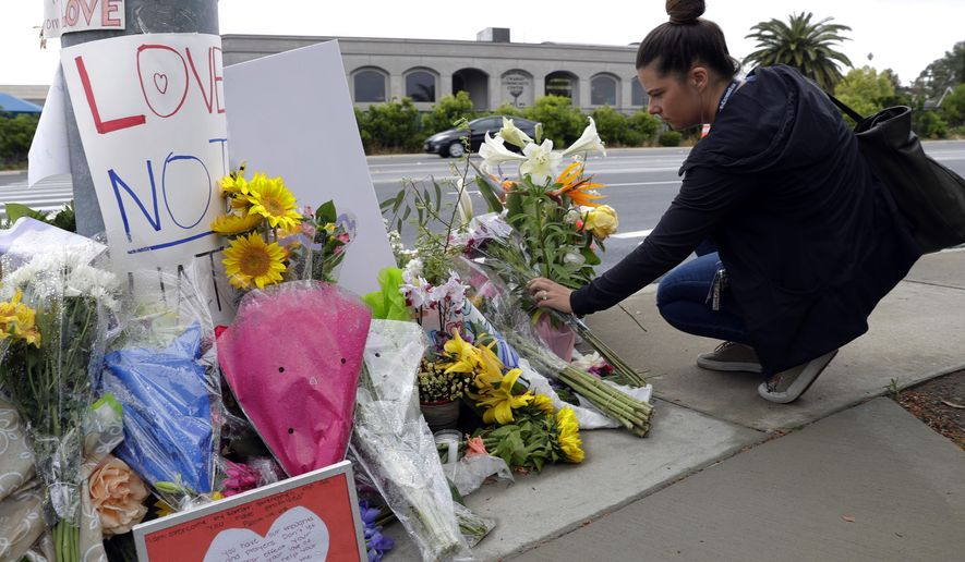 A woman leaves flowers on a growing memorial across the street from the Chabad of Poway synagogue in Poway, Calif., on Monday, April 29, 2019. A gunman opened fire on Saturday, April 27 as dozens of people were worshipping exactly six months after a mass shooting in a Pittsburgh synagogue. (AP Photo/Greg Bull)