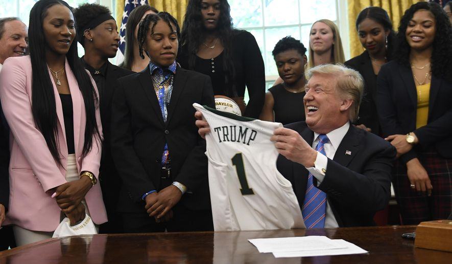 President Donald Trump holds up a jersey that was presented to him as he welcomed members of the Baylor women's basketball team, who are the 2019 NCAA Division I Women's Basketball National Champions, to the Oval Office of the White House in Washington, Monday, April 29, 2019. (AP Photo/Susan Walsh)