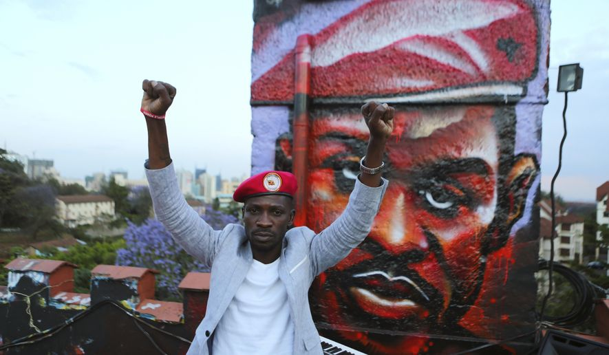 FILE - In this Friday Oct. 12, 2018 file photo, the Ugandan pop star and opposition politician known as Bobi Wine, whose real name is Kyagulanyi Ssentamu, poses next to a mural of himself during a visit to an activists' arts center in Nairobi, Kenya. Wine was remanded to jail on Monday, April 29, 2019 after being charged over his role in a street protest last year against a tax on social media. (AP Photo/Brian Inganga, File)