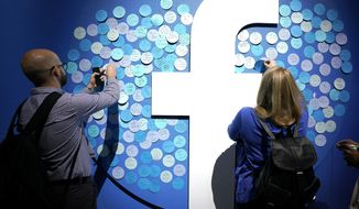 Attendees stick notes on a Facebook logo at F8, the Facebook's developer conference, Tuesday, April 30, 2019, in San Jose, Calif. (AP Photo/Tony Avelar )