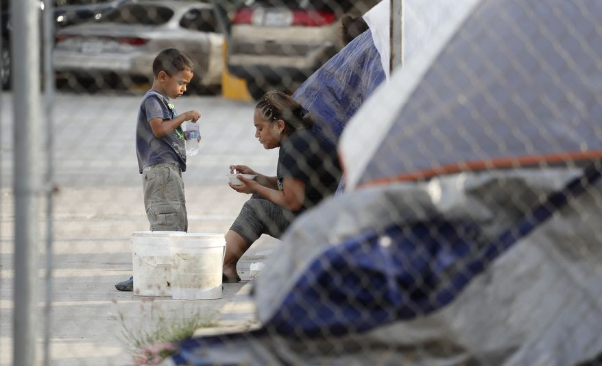 Suanny Gomez, 24, from Honduras and seeking asylum in the United States, waits in a tent with her 5-year-old son, William, Tuesday, April 30, 2019, in Matamoros, Mexico. Gomez said she does not have money to pay a proposed fee for seeking asylum. (AP Photo/Eric Gay) ** FILE **