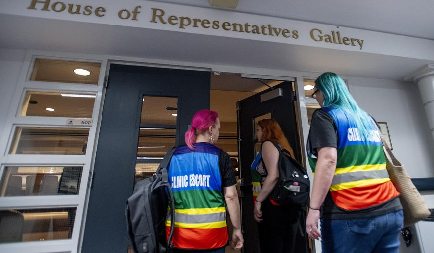 Women's heath clinic escorts, from left Mia Raven, Margeaux Hartline and Kari Crowe walk into the gallery to watch debate on the abortion ban bill at the Alabama Statehouse in Montgomery, Ala., on Tuesday April 30, 2019.  The House of Representatives on Tuesday will debate the proposal to make performing an abortion a felony. The bill contains an exemption for the mother's health but not for rape or incest.The legislation is purposely designed to conflict with the 1973 Roe v. Wade Supreme Court decision legalizing abortion nationally. (Mickey Welsh/The Montgomery Advertiser via AP)