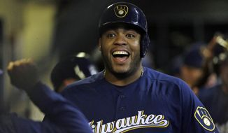 Milwaukee Brewers' Jesus Aguilar smiles in the dugout after hitting a three-run home run during the seventh inning of the team's baseball game against the Colorado Rockies on Tuesday, April 30, 2019, in Milwaukee. (AP Photo/Aaron Gash)