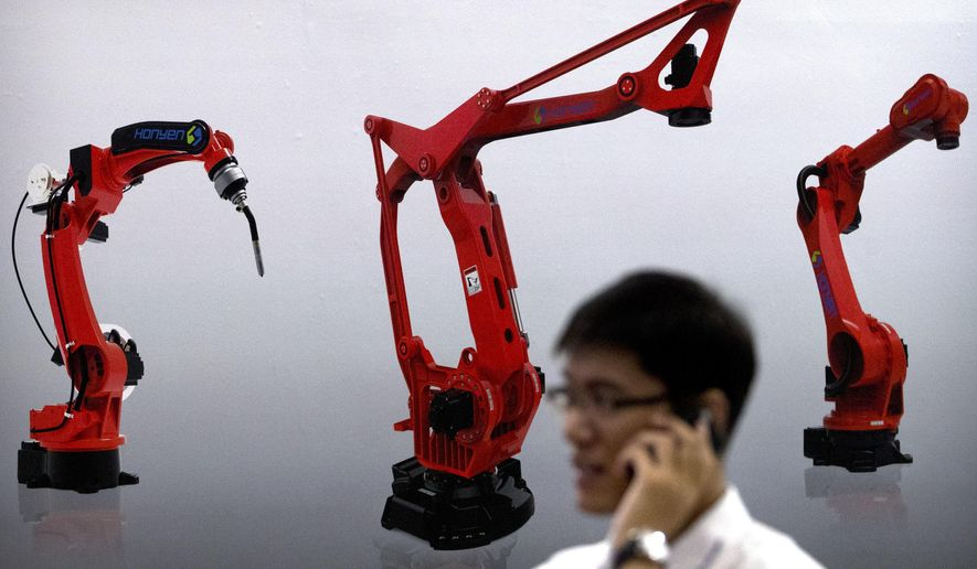FILE - In this Aug. 15, 2018, file photo, a visitor talks on his phone in front of a display of manufacturing robots from Chinese robot maker Honyen at the World Robot Conference in Beijing, China. Two surveys show Chinese factory activity grew in April but below the previous month's pace amid a tariff battle with Washington. (AP Photo/Mark Schiefelbein, File)