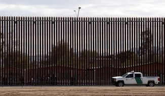 In this April 5, 2019, file photo, a U.S. Customs and Border Protection vehicle sits near a section of the U.S. border wall with Mexico in Calexico, Calif. (AP Photo/Jacquelyn Martin) ** FILE **