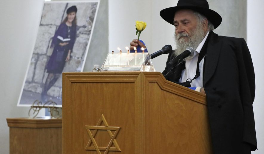 Yisroel Goldstein, rabbi of Chabad of Poway, holds a yellow rose as he speaks Monday, April 29, 2019, at the funeral for Lori Kaye, who is pictured at left, in Poway, Calif. Kaye, who was was killed Saturday when a gunman opened fire inside the Chabad of Poway synagogue, had given Goldstein the flower as part of a bouquet the day before the shooting, which also injured Goldstein. (AP Photo/Gregory Bull)
