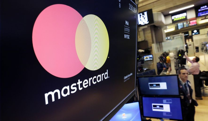 FILE - In this Oct. 31, 2017, file photo the logo for Mastercard is displayed on a screen above the trading floor of the New York Stock Exchange. Mastercard reports financial results Tuesday, April 30, 2019. (AP Photo/Richard Drew, File)