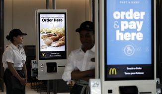 FILE - In this Aug. 8, 2018, file photo employees stand in McDonald's Chicago flagship restaurant. McDonald's Corp. reports financial results Tuesday, April 30, 2019. (AP Photo/Nam Y. Huh, File)