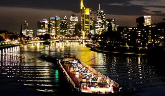 A cargo ship is seen on the river Main with the bank buildings in background in Frankfurt, Germany, late Wednesday, April 17, 2019. (AP Photo/Michael Probst)