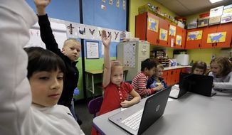 In this file photo taken on Nov. 4, 2015, kindergartner Lauren Meek, third left, raises her hand as she sits with second-grade students helping her on programming during their weekly computer science lesson at Marshall Elementary School in Marysville, Wash. Though less likely to study in a formal technology or engineering course, America's girls are showing more mastery of those subjects than their boy classmates, according to newly released national education data made public Tuesday, April 30, 2019. (AP Photo/Elaine Thompson, File)