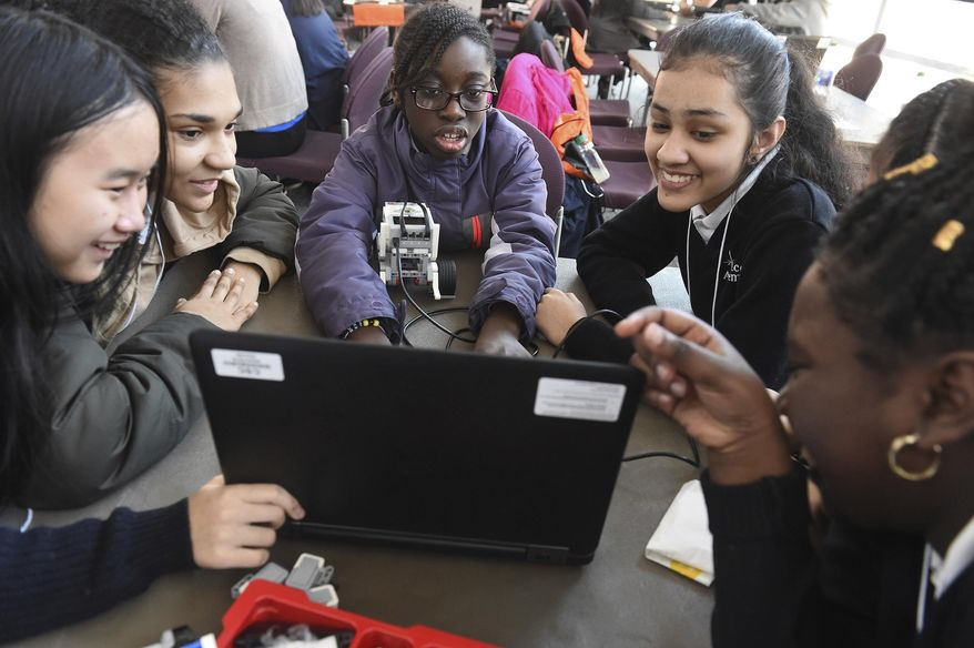 FILE - In this file photo taken Feb. 21, 2019, seventh grade students from Grace Academy in Hartford, Conn., work together on a robot using plans on a computer at the Connecticut Science Center in Hartford. Though less likely to study in a formal technology or engineering course, America's girls are showing more mastery of those subjects than their boy classmates, according to newly released national education data made public Tuesday, April 30, 2019. (Jim Michaud/Journal Inquirer via AP, File)