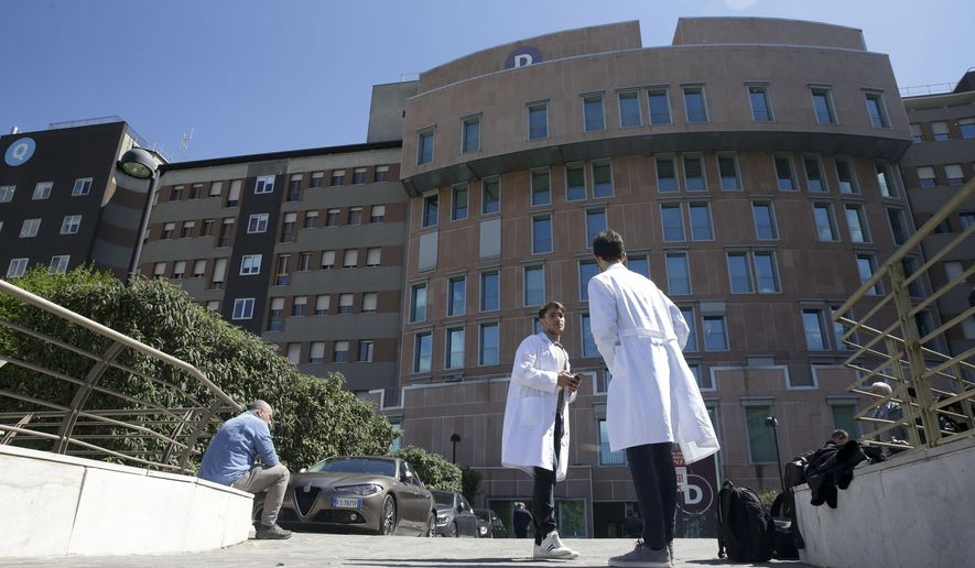 People stand outside Milan's San Raffaele hospital where former Italian Premier Silvio Berlusconi arrived, Tuesday, April 30, 2019. Berlusconi is in the hospital suffering from renal colic on the day he planned to present his candidates for European Parliament elections.(AP Photo/Luca Bruno)