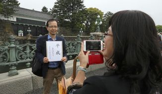 "Hitoshi Sato, a university official, with a sign reading ""Heisei, Thank you"" poses for a photo taken by his wife Yang Shufeng, from Taiwan, in front of Imperial Palace in Tokyo Tuesday, April 30, 2019. Japan's Emperor Akihito is set to abdicate later in the day as Japan embraces the end of his reign with an emotion mixed with reminiscence and hopes for a new era. (AP Photo/Eugene Hoshiko)"