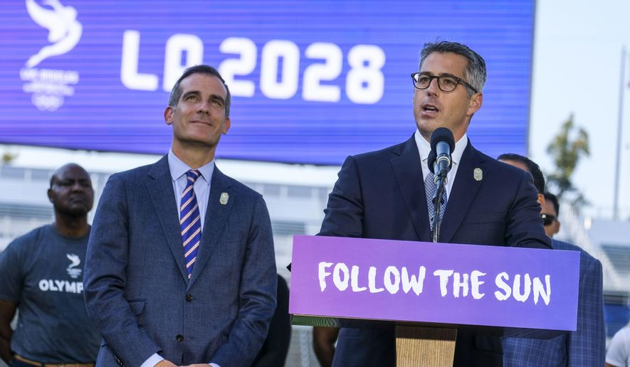 FILE - In this July 31, 2017, file photo, Los Angeles Mayor Eric Garcetti, left, listens as Los Angeles Olympic Committee leader Casey Wasserman speaks during a press conference to make an announcement for the city to host the Olympic Games and Paralympic Games 2028, at Stubhub Center in Carson, Calif. The price tag on the Los Angeles 2028 Olympics is now $6.88 billion, a $1.36 billion increase that comes mainly because of accounting measures designed to better reflect inflation over the long lead-up to those games. Most key numbers the organizing committee released Tuesday, April 30, 2019,  are essentially the same as those submitted in the original bid documents, only adjusted from 2016 dollars to reflect the real value of the dollars at the time they'll be received or spent. (AP Photo/Ringo H.W. Chiu, File)