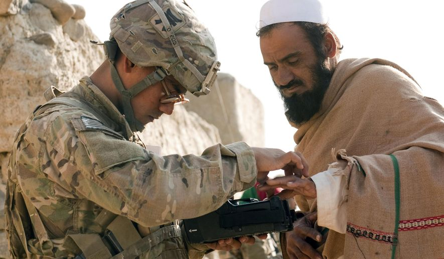 In this Nov. 5, 2012, photo provided by the U.S. Army, U.S. Army Pfc. Mark Domingo, left, takes an Afghan man's fingerprints in the village of Dande Fariqan, in Afghanistan's Khowst Province, as part of the military's effort to gather biometric data on the residents. Domingo, an Army veteran who converted to Islam and discussed launching various terror attacks throughout Southern California, was arrested as he plotted to bomb a white supremacist rally as retribution for the New Zealand mosque attacks, federal prosecutors said Monday, April 29, 2019. (Sgt. Christopher Bonebrake/U.S. Army via AP)