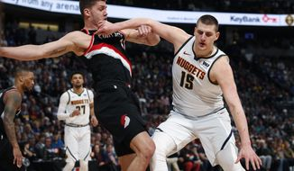 Denver Nuggets center Nikola Jokic, right, pushes off Portland Trail Blazers forward Meyers Leonard in the first half of Game 1 of an NBA basketball second-round playoff series Monday, April 29, 2019, in Denver. (AP Photo/David Zalubowski)