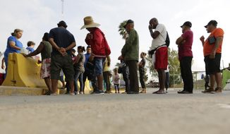 Migrants seeking asylum in the United States stand in line to receive breakfast from a group of volunteers in near the international bridge, Tuesday, April 30, 2019, in Matamoros, Mexico. President Donald Trump is proposing charging asylum seekers a fee to process their applications as he continues to try to crack down on the surge of Central American migrants seeking to cross into the U.S. (AP Photo/Eric Gay)