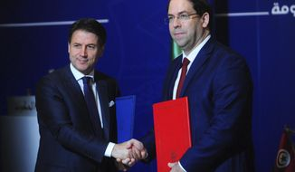 Tunisian Prime Minister Youssef Chahed, right, and Italian Prime Minister Giuseppe Conte, pose during a signature of agreements as part of an inter-governmental summit at the Kasbah Government palace, in Tunis, Tuesday, April 30, 2019. Italy's chief of government and an array of top ministers are visiting Tunisia, a leading strategic and economic partner whose shared concerns include migration and the North African country's unstable neighbor, Libya. (AP Photo/Hassene Dridi)