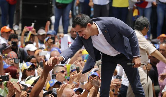 Venezuela's opposition leader and self proclaimed president Juan Guaido, greets the crowd during a rally in Caracas, Venezuela, Saturday, April 27, 2019. The Trump administration has added Venezuelan Foreign Minister Jorge Arreaza to a Treasury Department sanctions target list as it increases pressure on Guaido's opponent, embattled President Nicolas Maduro. (AP Photo/Fernando Llano)