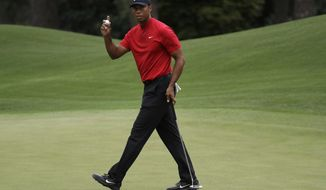 FILE - In this April 14, 2019, file photo, Tiger Woods waves on the eighth hole during the final round of the Masters golf tournament in Augusta, Ga.Harold Varner III worked up the courage to ask a favor of Tiger Woods for a close friend, Daniel Meggs, battling colon cancer. Woods made a videotape message for Meggs on the Wednesday of the Masters, offering encouragement to the former Wake Forest golfer to keep fighting and to never give up hope. (AP Photo/Chris Carlson, File)