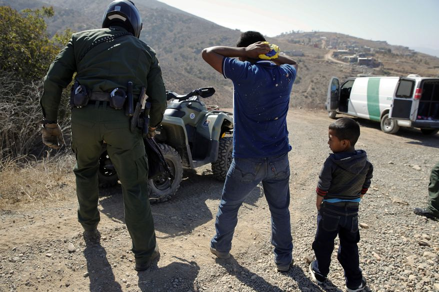 In this June 28, 2018, file photo, a Guatemalan father and son, who crossed the U.S.-Mexico border illegally, are apprehended by a U.S. Border Patrol agent in San Diego. California will introduce group trials on Monday, July 9, for people charged with entering the country illegally. Federal prosecutors in Arizona, Texas and New Mexico have long embraced these hearings, which critics call assembly-line justice. California was a lone holdout and the Justice Department didn't seriously challenge its position until the arrival of Attorney General Jeff Sessions. (AP Photo/Jae C. Hong, File)